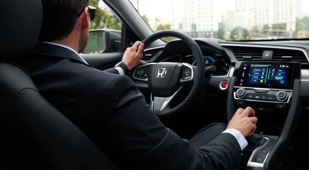 Homem a conduzir carro Honda