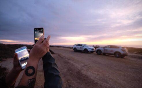 Duas mãos com telemóveis a fotografar CR-V e HR-V na Estrada Nacional 2