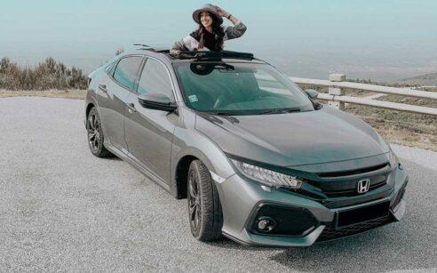 Rapariga no tejadilho de um Honda Civic Cinzento