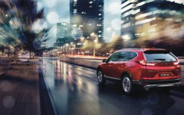 Carro Honda vermelho a conduzir com chuva